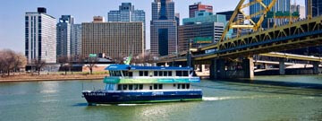 RiverQuest boat on a river with city of Pittsburgh in the background