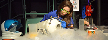 A live theater demonstration of a woman pouring liquid Nitrogen