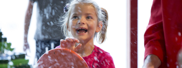 Young girl spins the wheel to make it rain at H2Oh's water table.