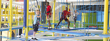 Three boys and a girl balancing on the ropes in SportsWorks