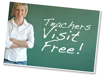"A chalkboard with ""teachers visit free!"" on it and a smiling woman standing next to it"
