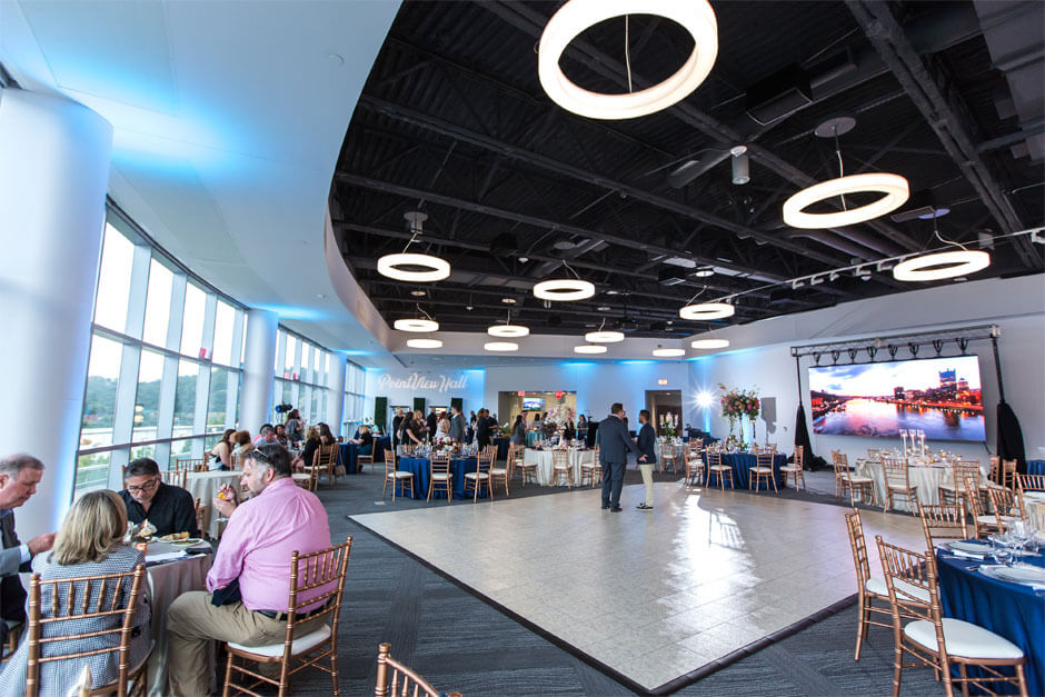 Interior of PointView Hall, tables, chairsm and dance floor. Men and women in business attire are sitting and eating at round tables. There is a presentation screen showing a daytime picture of the Pittsburgh Skyline.