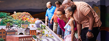 A mother smile as her family of four looks at the railroad display in awe