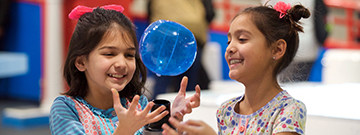 Two girls laugh as they interact with a small floating ball