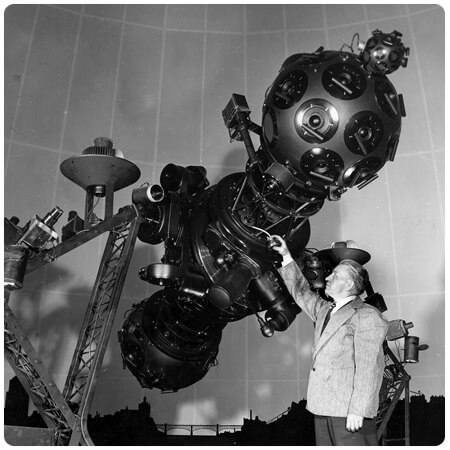 Black and white photo of man in suit with Zeiss Projector